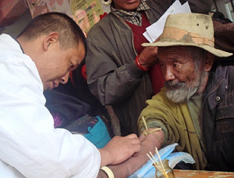 Man Collecting a blood sample from a Tibetan subject