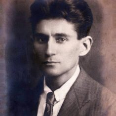 Black/white photo of Franz Kafka with purplish, bluish discoloration
